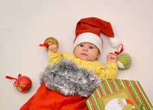 The baby in a New Year's suit of Santa Claus with Christmas tree decorations. On a light background stock photography