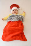 The baby in a New Year's suit of Santa Claus on a light background backgrou. The baby in a New Year's suit of Santa Claus stock photo