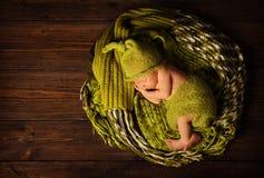 Baby newborn portrait, kid sleeping in woolen hat. On brown wooden background Royalty Free Stock Images