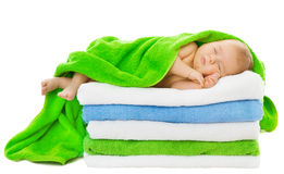 Baby newborn sleeping wrapped in bath towels. Over white background Royalty Free Stock Photo