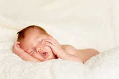 The baby, newly born, lies on the plaid and sleeping, handle the person Stock Photos