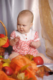 Baby next to a basket of apples Royalty Free Stock Images