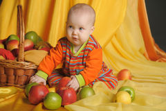Baby next to a basket of apples Stock Image