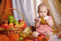 Baby next to a basket of apples Stock Photo