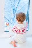 Baby next window to snowy garden on Christmas day Stock Photos
