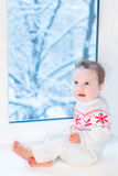 Baby next window to snowy garden on Christmas day Royalty Free Stock Photos