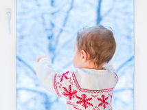 Baby next window to snowy garden on Christmas day Royalty Free Stock Images