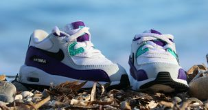 Baby Nike Air Max Sneakers. Roquebrune-Cap-Martin, France - September 26, 2019: White And Purple Baby Boy Nike Air Max Shoe With The Waves Of The Sea In The stock footage
