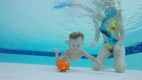 Baby nimmt ein Spielzeug von Unterwasser eines Pools unter der Steuerung der Mutter auf stock video footage