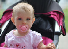 Baby with nipple sitting in pram. Little baby girl with nipple sitting in pram Royalty Free Stock Images