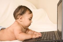 Baby with notebook portable computer, typing Royalty Free Stock Photo