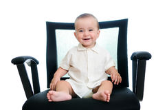 Baby in office armchair. A smiling baby girl sitting in an office chair, wearing a white shirt. isolated in white Royalty Free Stock Photos