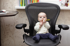 Baby on office chair Stock Photography