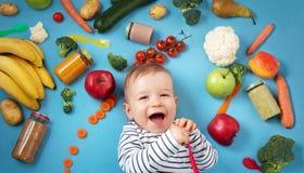 Baby omgav med frukter och grönsaker Arkivbild