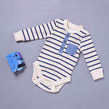 Baby onsie and toy over blue background Royalty Free Stock Photo