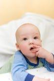 Baby op bed gezette vingers in mond Stock Foto