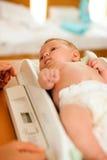 Baby op gewichtsschaal Royalty-vrije Stock Afbeeldingen