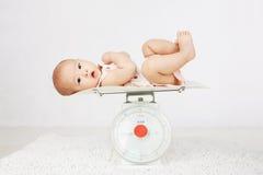 Baby op het wegen schaal Stock Fotografie