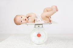 Baby op het wegen schaal Stock Foto's