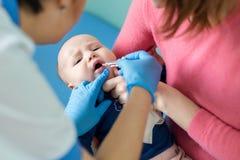 Baby op moedershand bij het ziekenhuis Verpleegster die zuigeling tot mondelinge inenting maken tegen rotavirusbesmetting Kindere royalty-vrije stock afbeelding