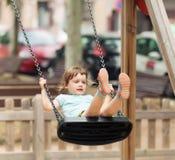 Baby op schommeling in stad Royalty-vrije Stock Afbeeldingen