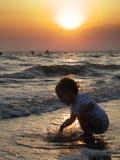 Baby op zonsondergangstrand Stock Foto
