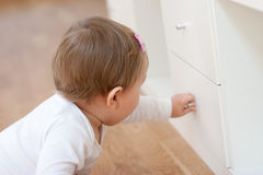 Baby opening a drawer Royalty Free Stock Photography