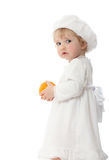 Baby with orange isolated on white. Studio portrait of baby with mellow orange in white clothes isolated on white Royalty Free Stock Photography