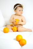 Baby with oranges Stock Images