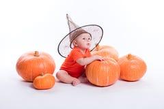 Baby in oranje t-shirt op een witte zitting als achtergrond in een witche royalty-vrije stock afbeeldingen
