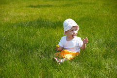 Baby outdoors. On the grass Stock Photo