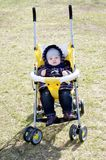 Baby outdoors on yellow baby carriage in spring Royalty Free Stock Photography