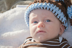 Baby Outside Wearing Knit Hat. Sweet baby boy wearing knit hat with brown and blue outfit lying on his back Stock Images