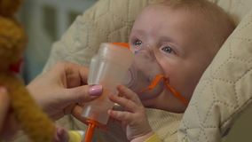 Baby With Oxygen Mask. Sitting in highchair child newborn boy caucasian white european 5 month old with soft plush toy brown bunny health care medical treatment stock footage