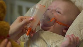 The Baby In Oxygen Mask. Sitting in highchair child newborn boy crying caucasian white european 5 month old with soft plush toy brown bunny health care medical stock video