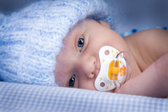 Baby with pacifier. Portrait of sleepy baby boy in woollen hat with pacifier or dummy royalty free stock photos