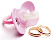 Baby Pacifier And Wedding Rings, Conceptual Stock Image