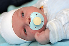 Baby with pacifier in bed Stock Photography