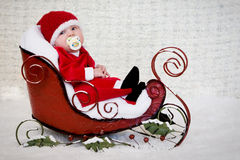 Baby with pacifier in Christmas sleigh Royalty Free Stock Photos