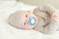 Baby with pacifier. Little baby with pacifier on the bed stock photo
