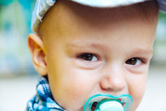 Baby with pacifier. Outside in the summer royalty free stock photo