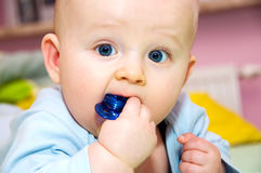 Baby and pacifier portrait. Baby lying on bed on belly and playing with pacifier royalty free stock images