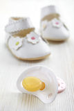 Baby pacifier and shoes Stock Photo
