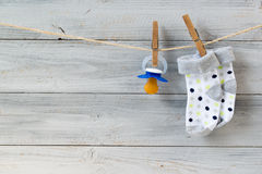Baby pacifier and socks hanging on clothesline on wooden background royalty free stock photos