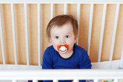 Baby with pacifier in white bed Stock Images