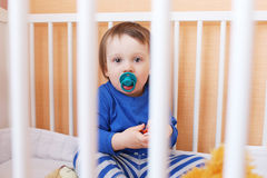 Baby with pacifier in white bed Stock Photo