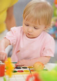 Baby painting on Easter eggs Stock Photos