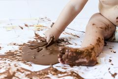 Baby painting with hands with chocolate Royalty Free Stock Photo