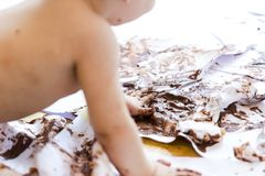 Baby painting with hands with chocolate Stock Photography