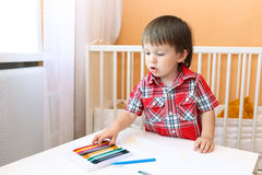 Baby painting with wax pencils at home Stock Photo